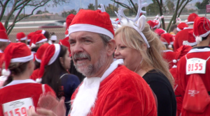 Executive Director, Ed Guthrie, of Opportunity Village, cheers on the 5K Santas, as they start the race.      Photo: Monique Gaudin